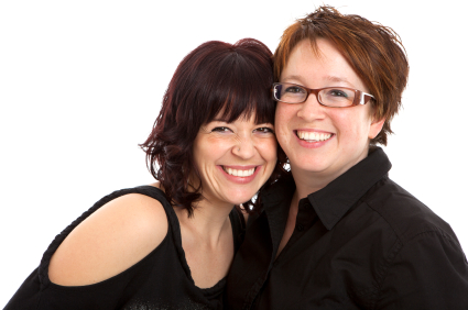 Two woman smiling holding each other close