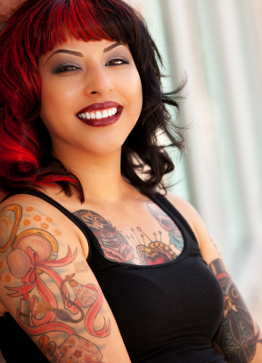 Woman with tattoos and red hair smiling
